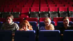 Four people in dark hall cinema watching film and hid from fear - stock footage