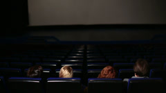 Four people in dark hall cinema get up and go after the movie Stock Footage