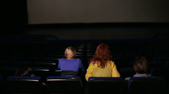 Heads of four discussing people in the dark hall cinema Stock Footage