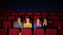 Four people in cinema watching the film then jump and rejoice Stock Footage