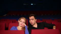Young man and woman very much afraid then smile in cinema hall Stock Footage
