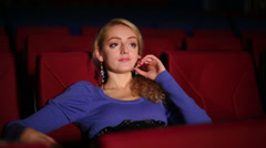 Young cute girl seats in cinema hall and watching film Stock Footage