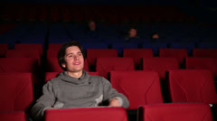 Young man experiencing different emotions at movie theater Stock Footage