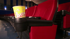 Popcorn yellow cup is stand at red seat in cinema Stock Footage