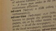 Stock Video Footage of Word Advertise in a dictionary with focus on the word
