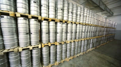 Review many rows of metal beer kegs in large warehouse Stock Footage