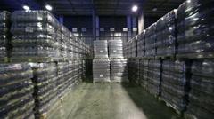 Rows of beer bottles in large dark warehouse brewery Stock Footage