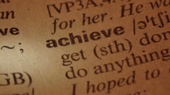 Word Achieve in a dictionary Stock Footage