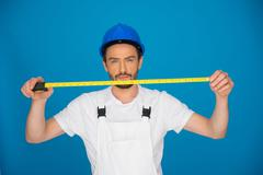 Young builder holding up a measuring tape Stock Photos