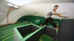 Agile guy overcomes obstacles on place for parkour training - stock footage