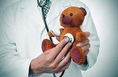 Doctor auscultating a teddy bear with bandages in its head and arm Stock Photos