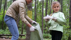 Mother with daughter helping clean up green forest - stock footage