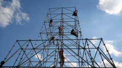 Workers working on tall scaffolding against a blue sky Stock Footage