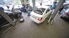White car leaves the lift at workshop Automir on Baikalskaya Stock Footage