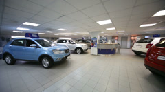 Review hall with clients desk and colored cars in office Stock Footage
