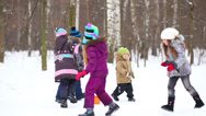 Stock Video Footage of Five children run around in winter park with snow and trees