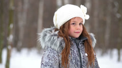 Cute little girl in grey jacket with fur collar and knitted hat - stock footage