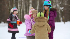 Children turn around tugging hands in winter park Stock Footage