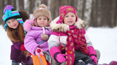 Girl pushes sledges with two younger children in winter park Stock Footage