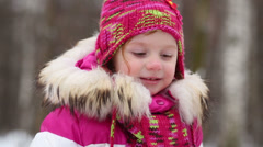 little girl in pink jacket with fur collar and knitted hat - stock footage