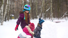 Three children throw snowballs from the snow wall guard Stock Footage