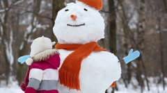 Little girl touch snowman in orange hat and scarf at winter park Stock Footage