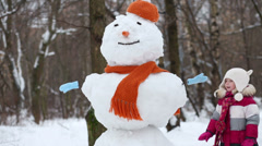 Little girl walk around snowman in orange hat and scarf Stock Footage