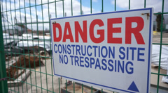 Danger construction sign in front of construction site Stock Footage