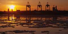 Cranes unload ship at commercial port during iceberg sunset 7 - stock footage