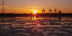 Cranes unload ship at commercial port during iceberg sunset 5 Stock Footage