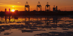 Cranes unload ship at commercial port during iceberg sunset 4 - stock footage