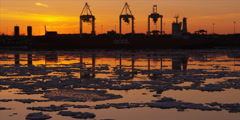 Cranes unload ship at commercial port during iceberg sunset 3 Stock Footage