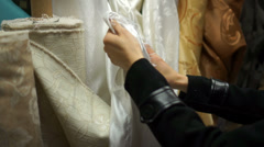 Hands examine the material in a fabric shop Stock Footage