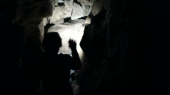 Man explores cave with light in narrow cave - stock footage