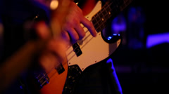 Bass player plays guitar with acoustic guitar in foreground - stock footage
