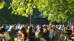 Tourists Crowds enjoy Beer at Beer garden Chinese Tower English Garden park Stock Footage