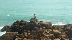Man sitting on a huge boulder on a beach and looking at the sea Stock Footage