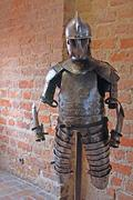 Suit of medieval armour in front of brick wall Stock Photos
