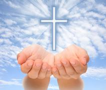 Hands holding Christian cross with light beams over sky Stock Photos