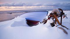 Small row boat laying on a pebble beach covered in snow Stock Photos