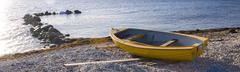small row boat laying on a pebble beach - stock photo