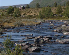 Flowing stream in tundra + log cabin in glacial landscape - Norway Stock Footage