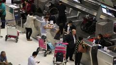 Passengers at check-in counters at Suvarnabhumi Airport, Bangkok Stock Footage