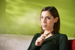 young woman smoking electronic cigarette at home - stock photo