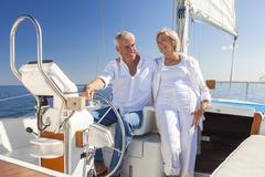 Happy senior couple sailing yacht or sail boat Stock Photos