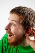 Listen - funny curious man with hand at ear Stock Photos