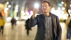 Man taking photo with camera phone at night Stock Footage