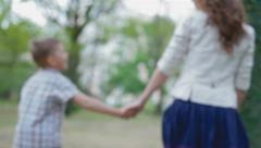 Mother and son walking in the park holding hands Stock Footage