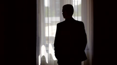 Stock Video Footage of silhouette of stylish man in suit looking out the window