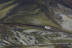 white 4x4 bus on a road in highlands, iceland - stock photo